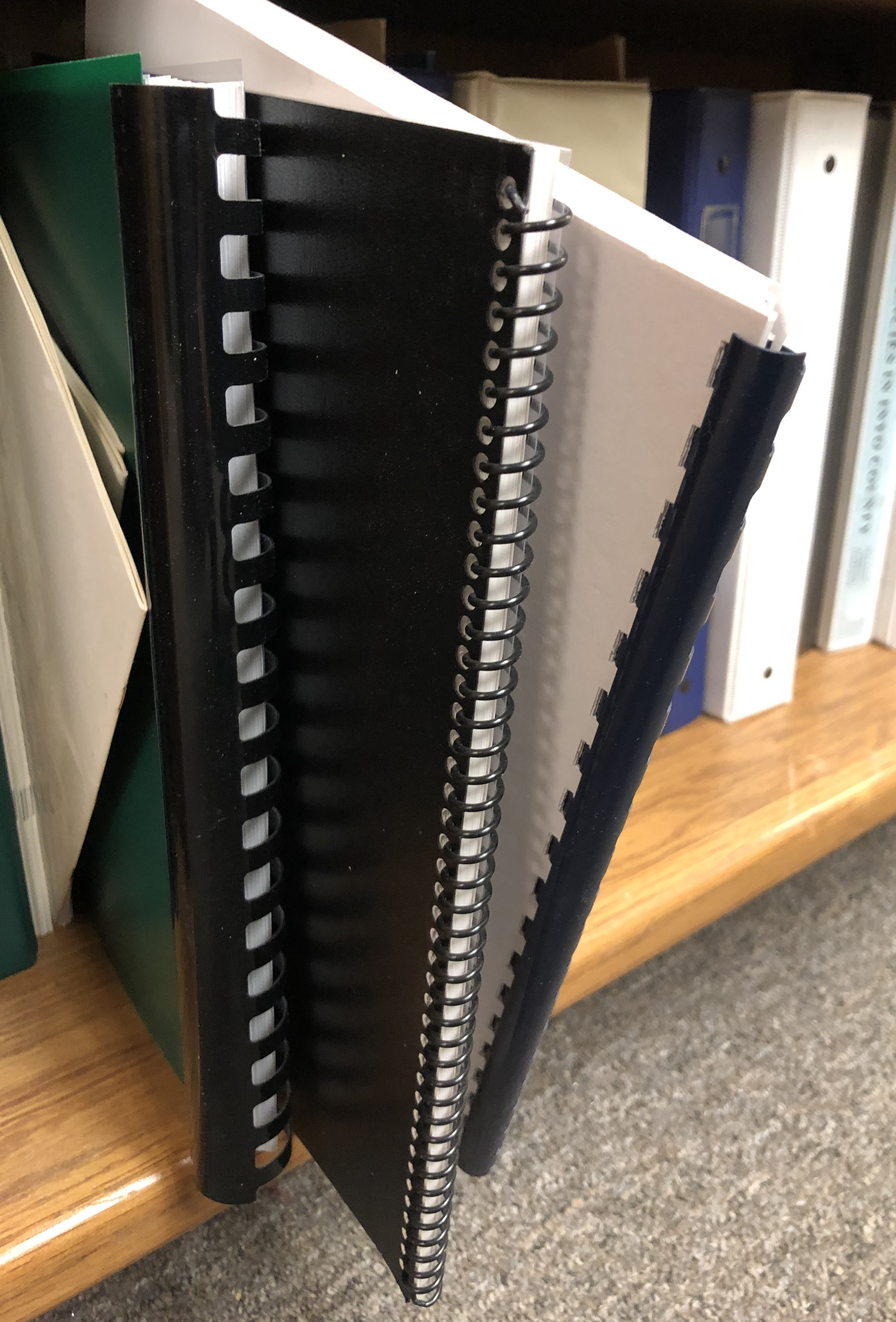 Multi-sized spiral-bound reports sticking out from bottom level of book shelf.