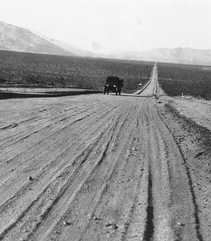Early 1900s model vehicle driving on dirt road through Eastern Sierra.
