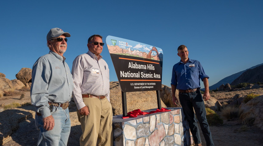 Supervisors Pucci and Kingsley to the left and Supervisor Griffiths to the right of a large sign announcing the new Alabama Hills National Scenic Area