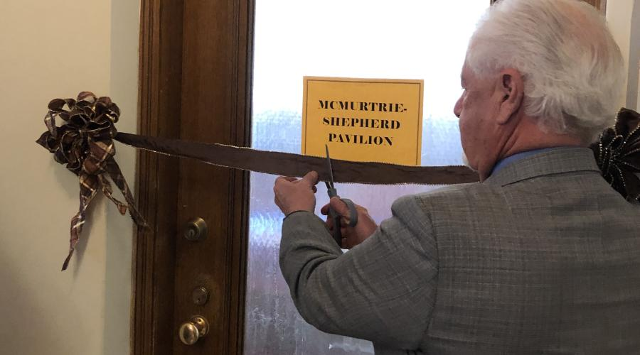Man uses scissors to cut ribbon strung across doorway