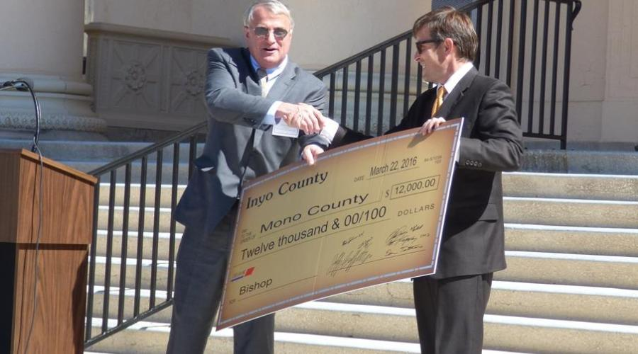 Two men in suits on courthouse steps shake hands over giant novelty check
