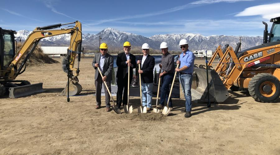 Five men wearing hard hats and holding shovels near construction equipment.