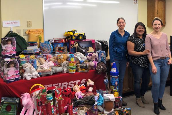 Three women standing next to table of toys