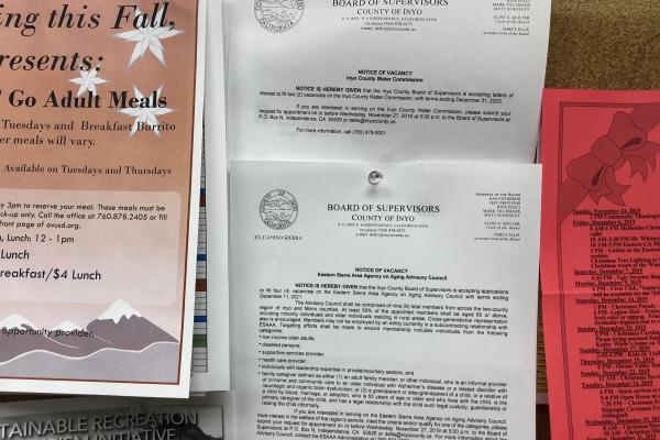 Bulletin board with flyers, including two advertising notices of vacancy for the Inyo County Water Commission and Eastern Sierra Area Agency on Aging Advisory Committee